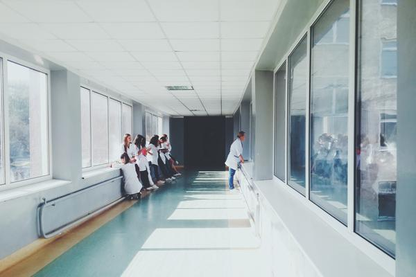 Health care workers stand in a hospital hallway