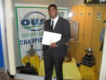 Rahim at his graduation in front of the OUA trophy
