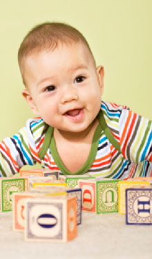 Smiling baby with toy blocks