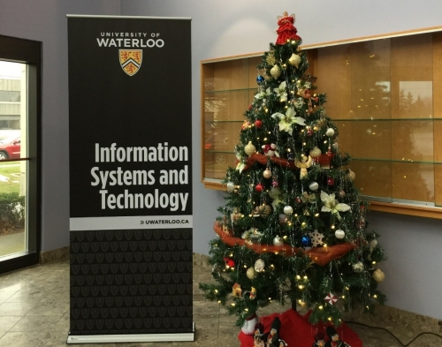 Information Systems and Technology sign with Christmas tree in lobby of East Campus 2.
