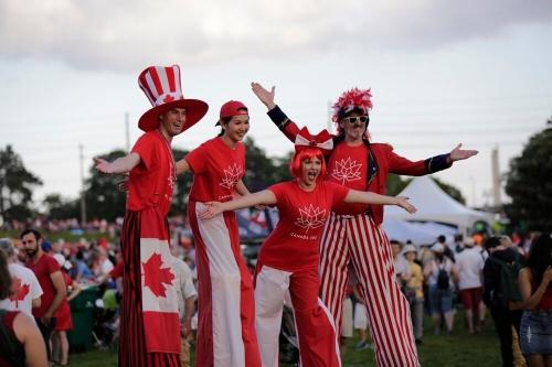 People dressed in Canadian flags on stilts