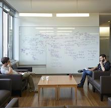 Deux étudiants discutant quantique devant un tableau blanc