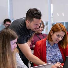 3 étudiants discutant du quantum sur un ordinateur portable