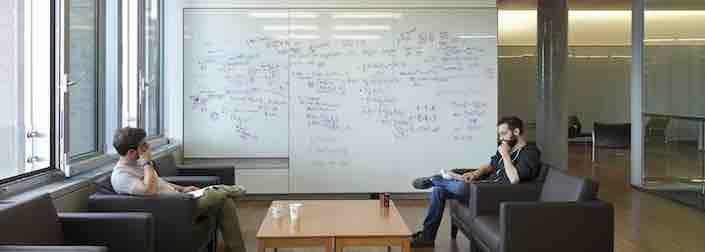 Deux étudiants discutant quantique devant des tableaux blancs