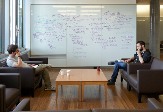 Two male IQC students discussing their ideas in front of a white board covered with equations