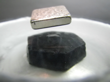 a square magnet levitating over a black chunk of superconductive material sitting in a dish of liquid nitrogen