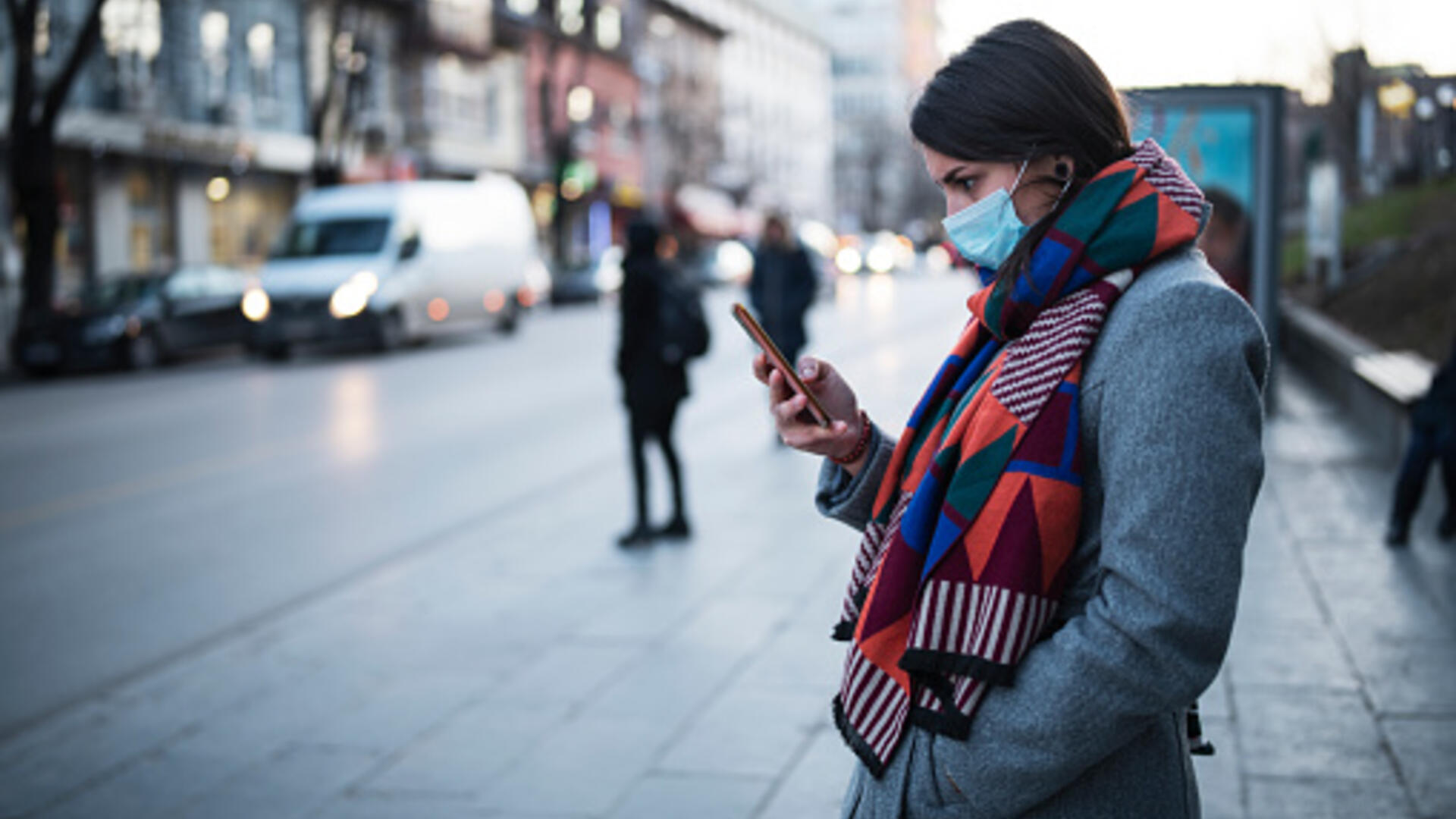 Women on a phone wearing a mask