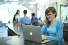 Girl in blue top on a laptop