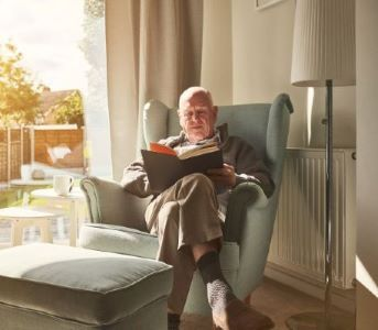 Older man reading book in green armchair