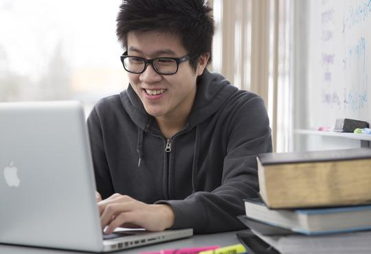 Student studying with a computer and books.
