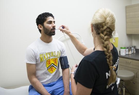 Nurse taking a student's temperature.