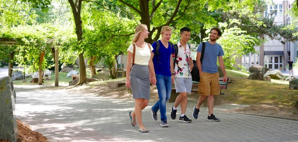 Four exchange students walking through the rock garden at the University of Waterloo on a sunny day