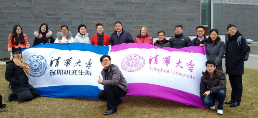 Delegates from Shenzhen Tsinghua University and Waterloo partners hold Tsinghua flags.