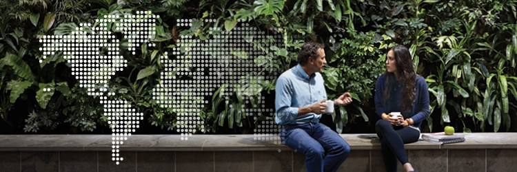 World map made of dots on top of an image of two people talking in front of a green, living wall composed of plants