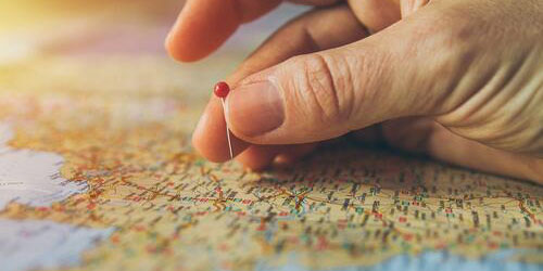 Person holding pin on map