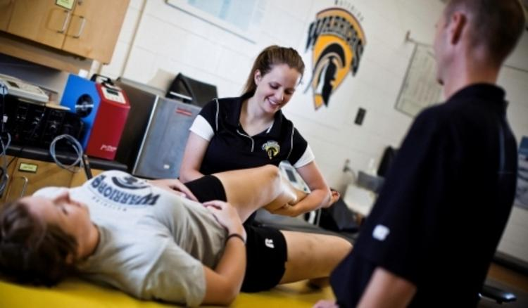 Student therapist checks athlete's leg in athletic therapy clinic.