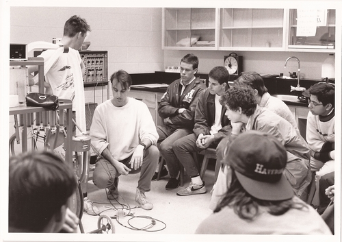 High school students watch a demonstration in a lab.