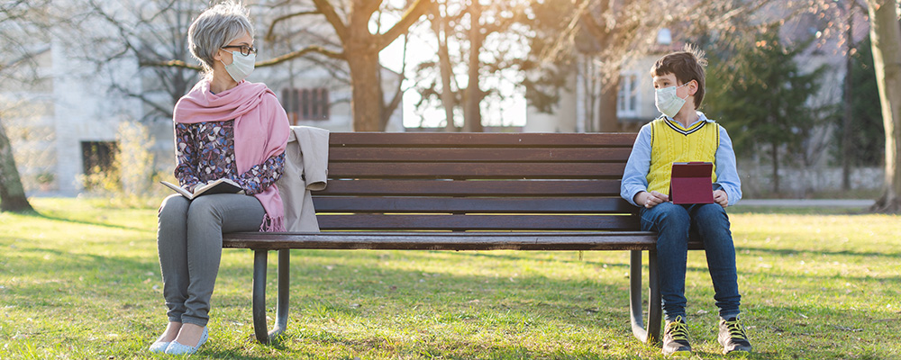 Young and older persons with masks on park bench, looking at each other