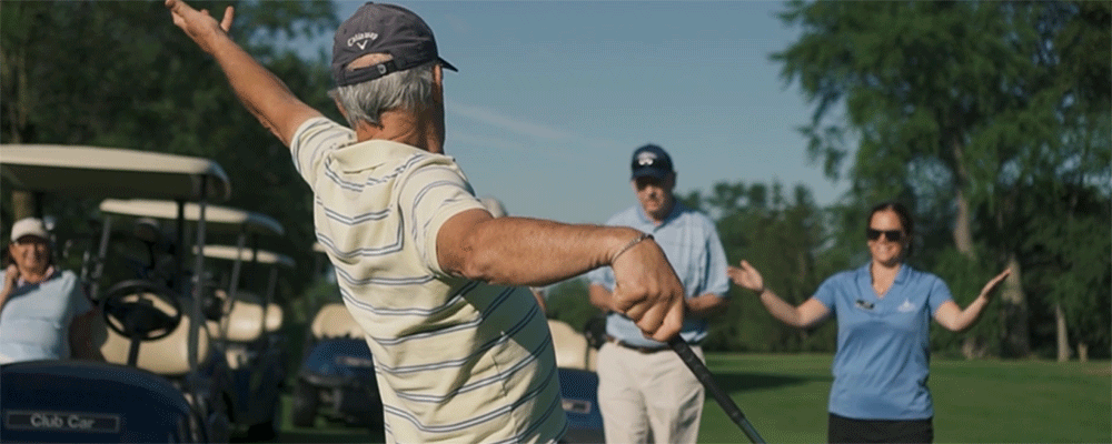 Older man playing golf with his hands in the air while other golfers watch.