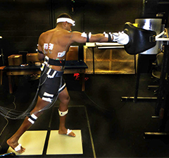 Brendan with sensors attached to his body while he punches a punching bag.