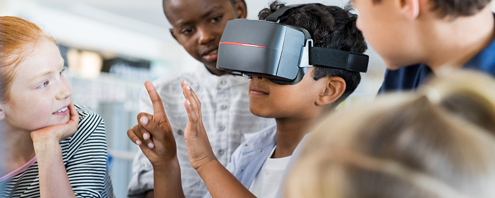 Child looking through VR goggles while others look on