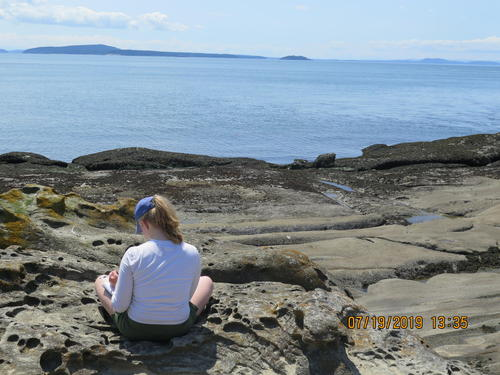 student sitting on rocky shore writing in journal