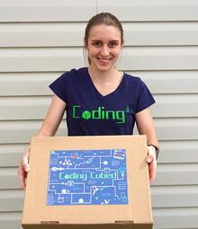 Cassidy holding the coding curriculum kit
