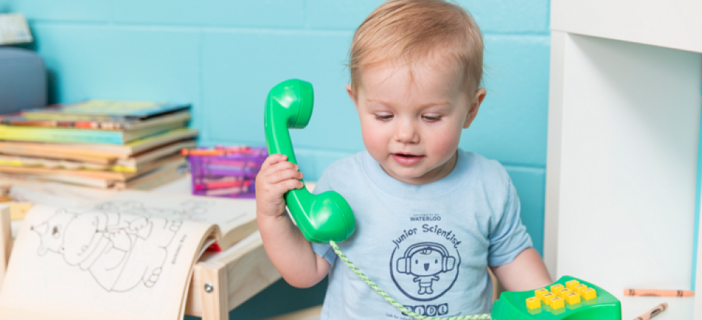 A baby with a toy phone