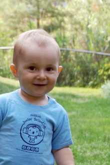 Baby smiling wearing a Lab for Infant Development and Language t-shirt