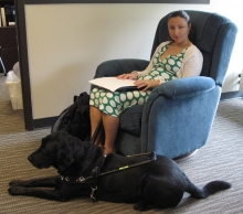 Student reading her braille document while sitting on the most comfortable chair on campus. Her guide dog is at her feet.