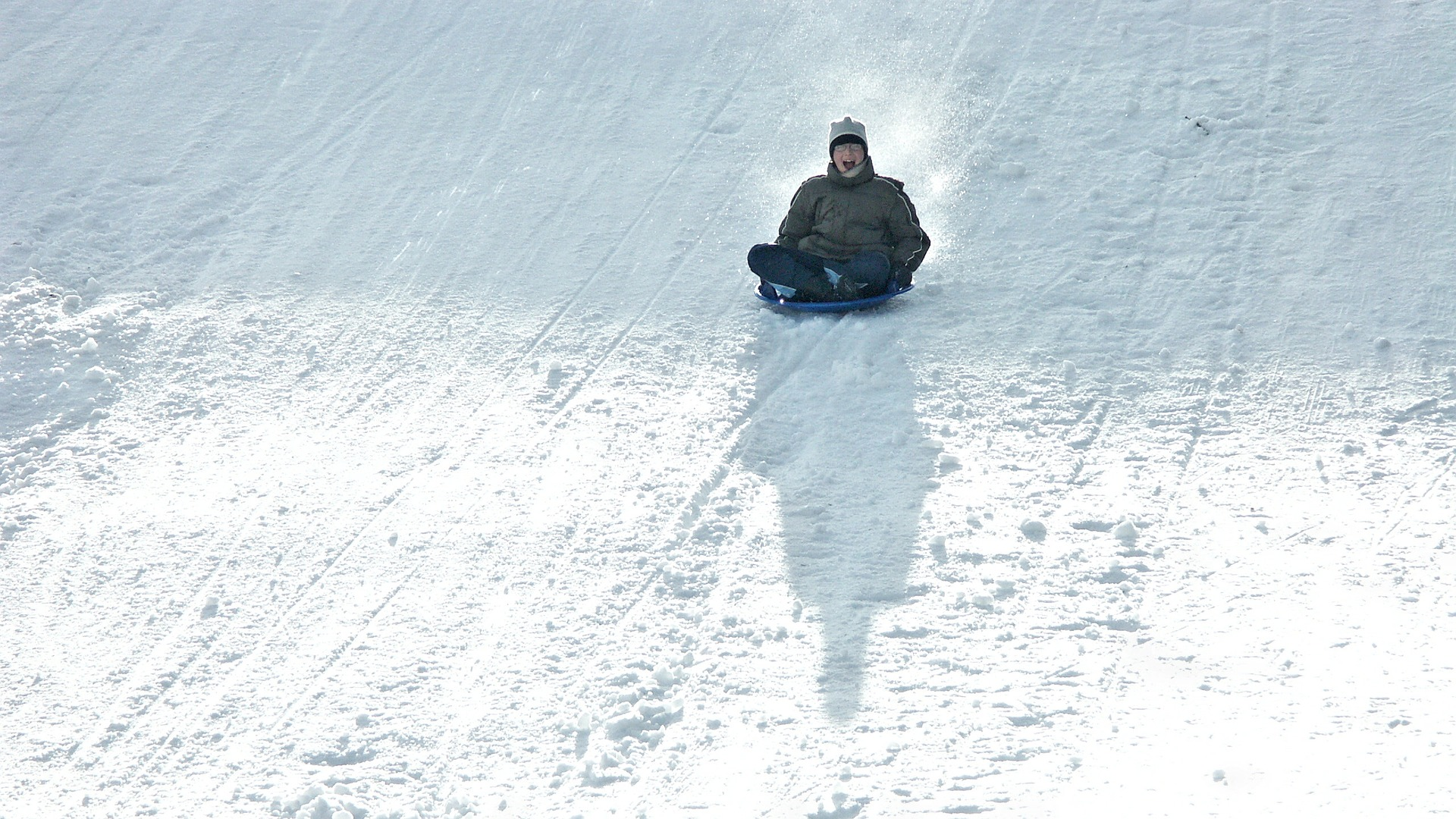 person in sledding downhill