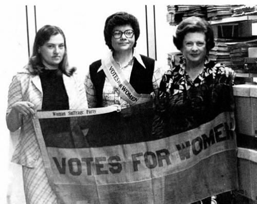 Women holding suffragette banner