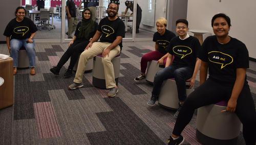 five people sitting on stools