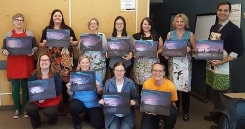 Staff holding paintings of northern lights
