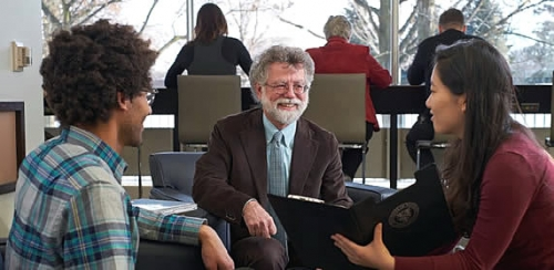 Mark Haslett in conversation with students in the lounge area of the Dana Porter Library.