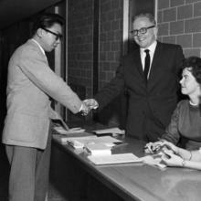 Image of Boris Kou shaking hands with a smiling Douglas Wright over a registration table as two seated students, Diana McDonald and Beverley Hollatz, look on.