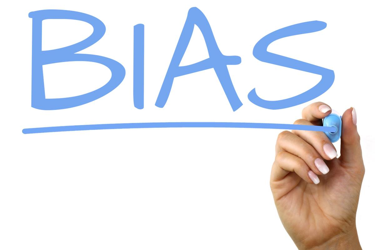 "hand writing the word ""bias"" in blue marker"