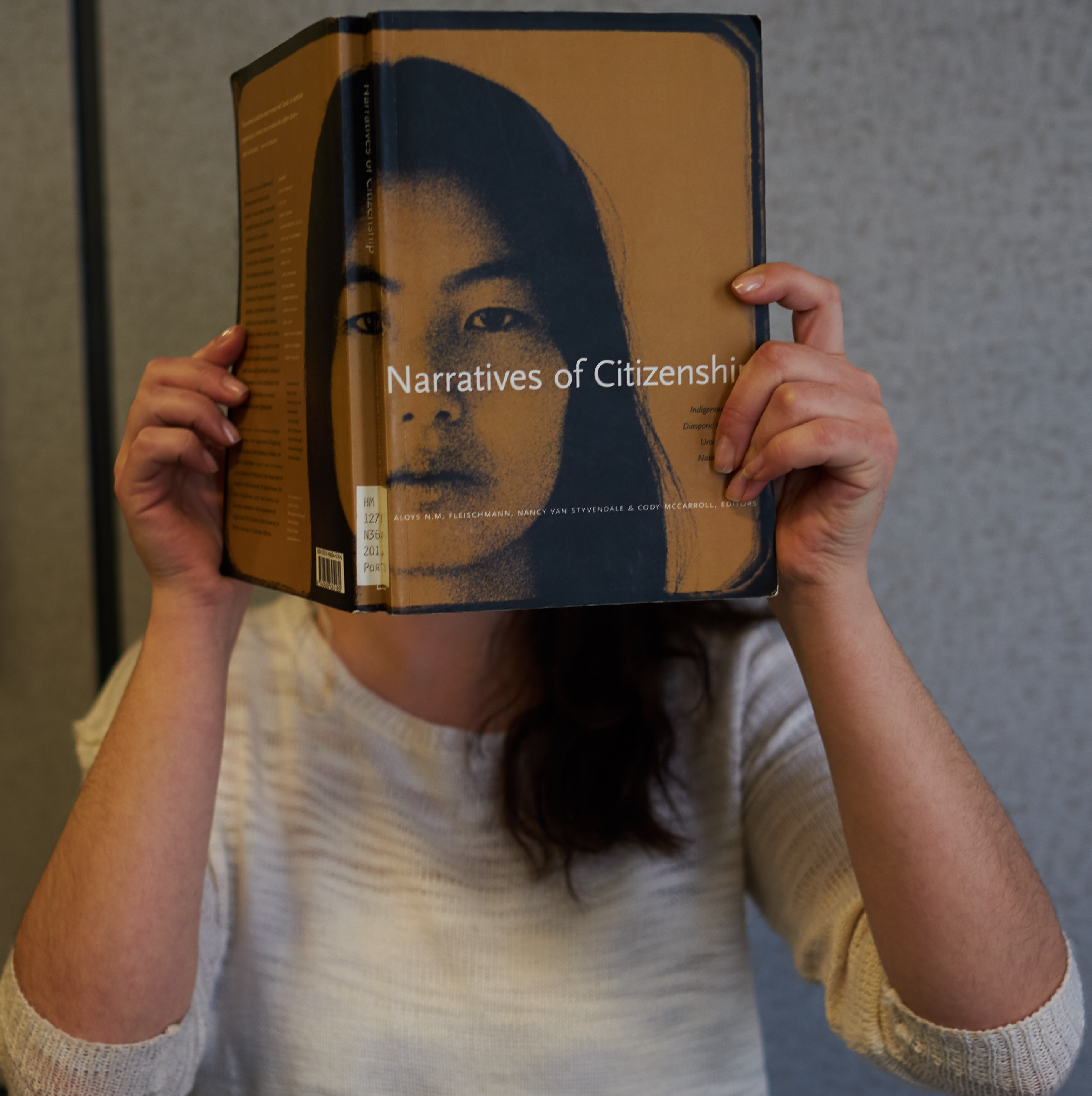 "Person holding the book ""narative of citizenship' in front of their face"