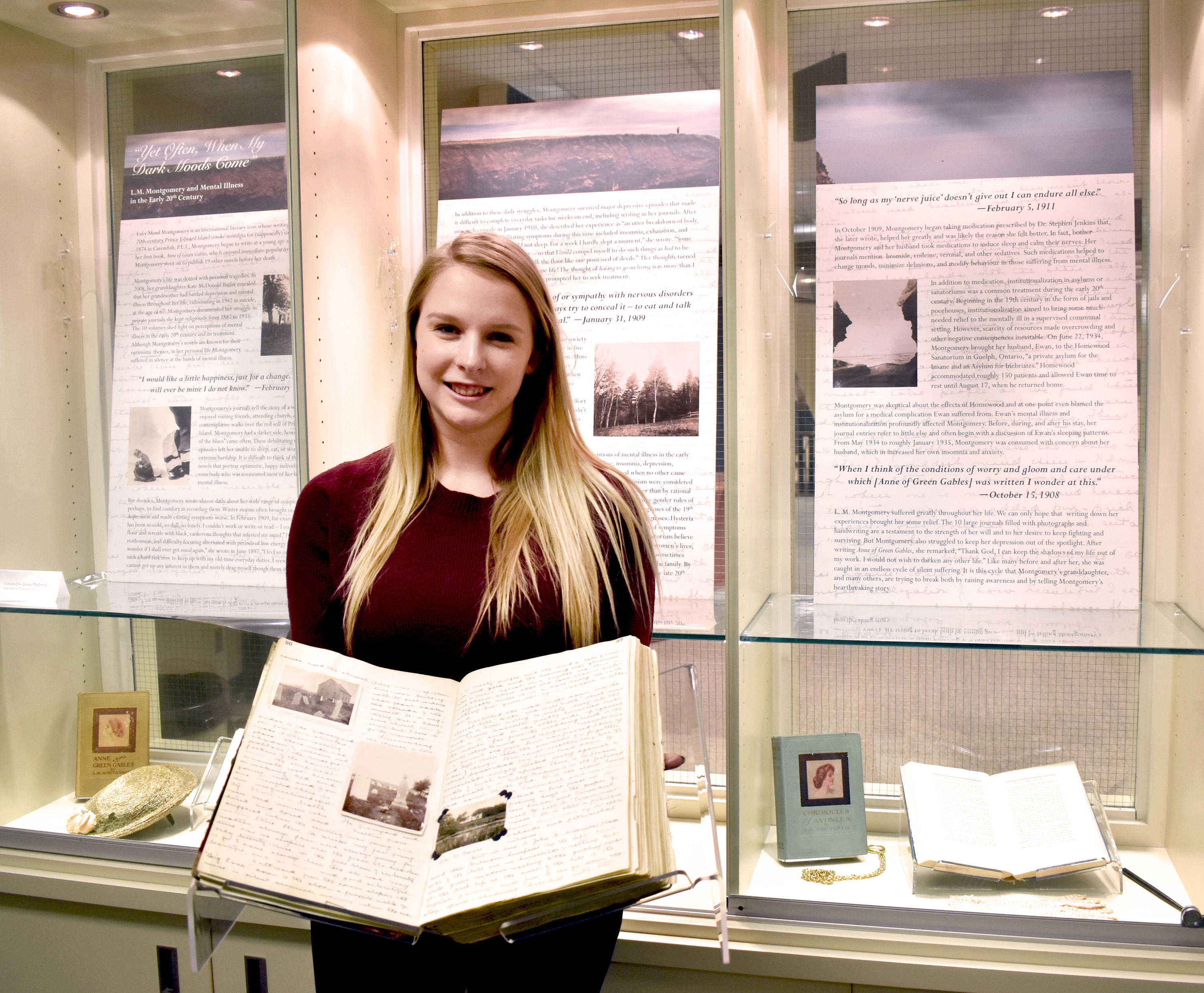 Jenna holding journal in front of display