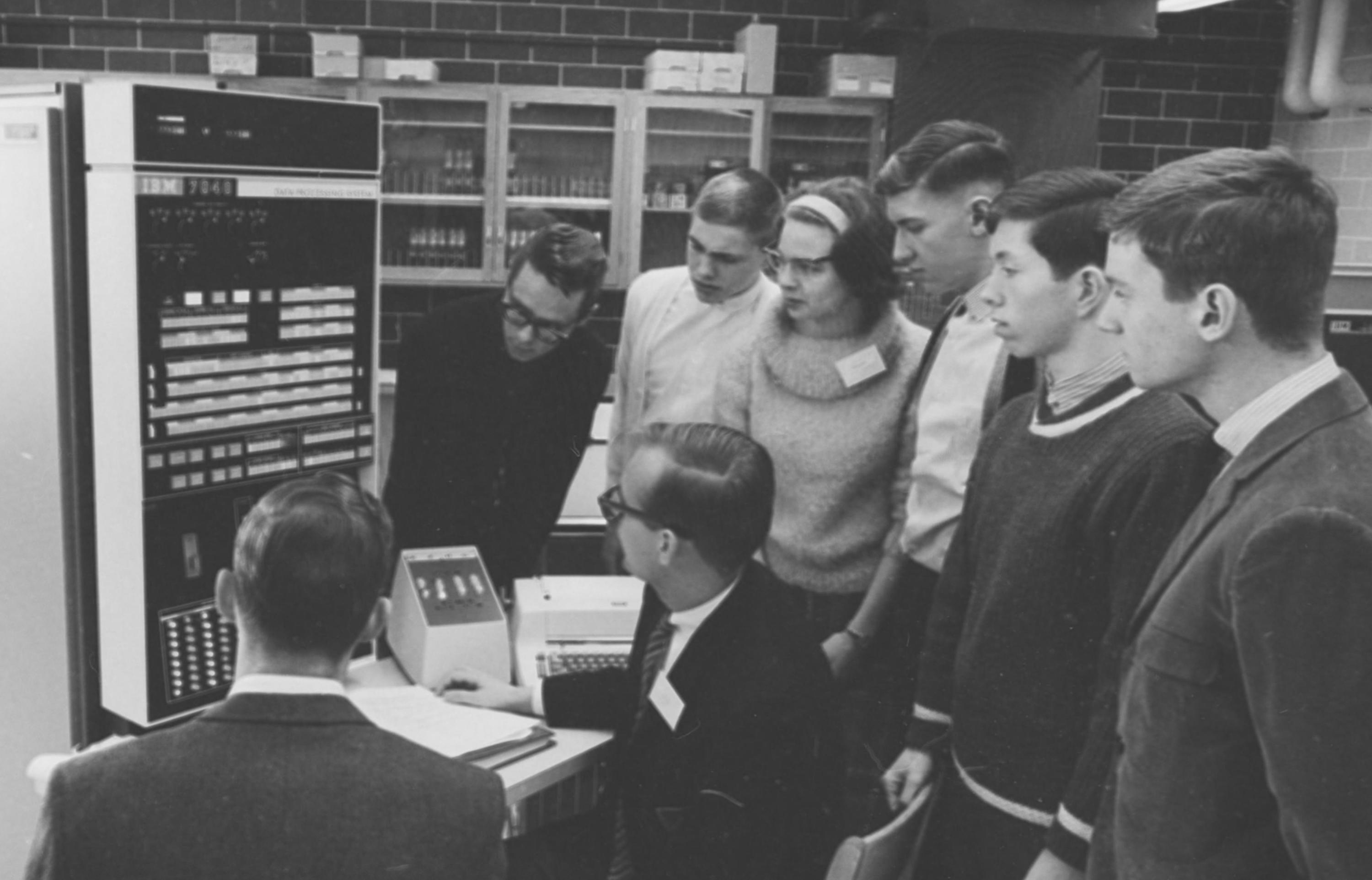 Image of Donald Cowan seated while explaining a computer to high school students.