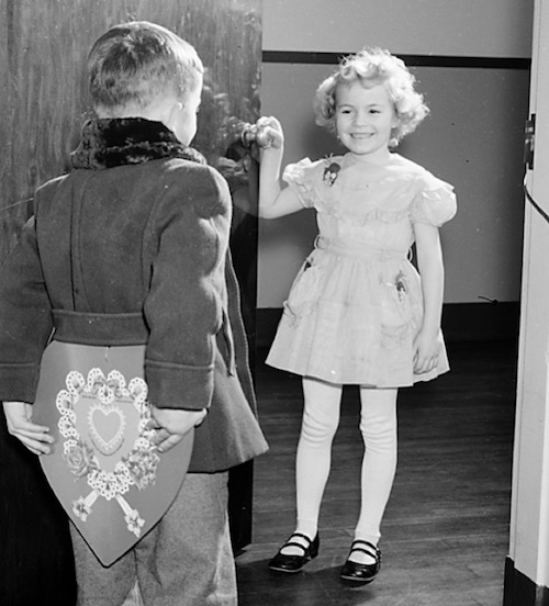 boy holding valentine behind back