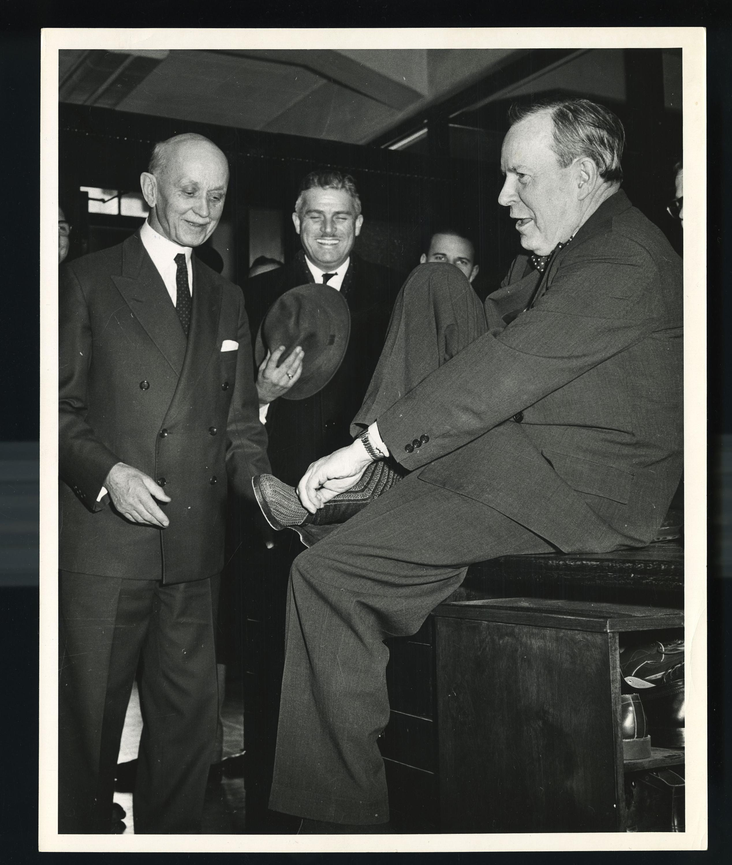 Lester B. Pearson tries on a pair of Kaufman shoes.
