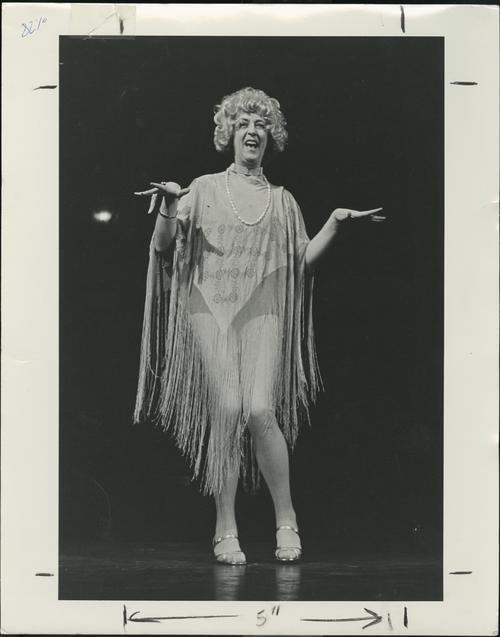 John Herbert during his acting performance wearing a dress, wig, and heels.