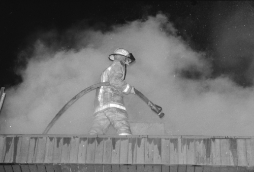 Fire fighter on roof with smoke