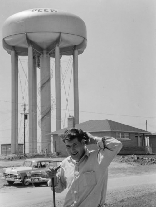 student with hose and water tower in background