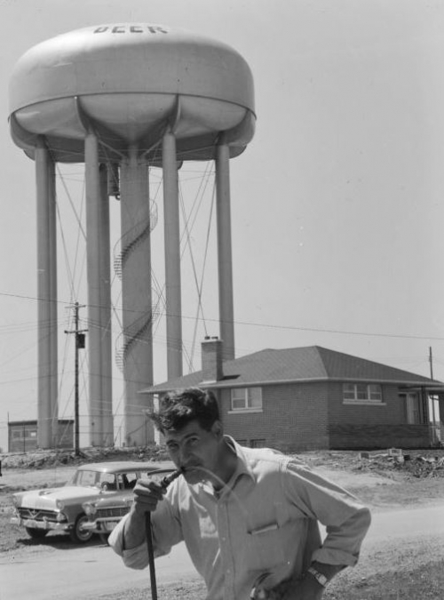 student drinking out of hose with water tower in background