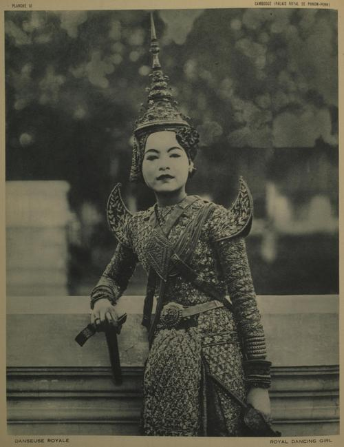 Dancer in costume, leaning against a fence.