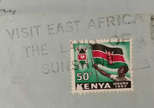 Stamp featuring a coat of arms and a citizen holding the Kenyan flag