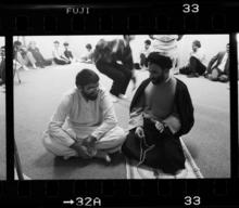 Two men sit next to each other on the floor, having a conversation with one another.