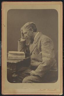 Portrait of an older man in a coat reading a book